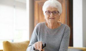 Blije oudere dame in haar woonkamer