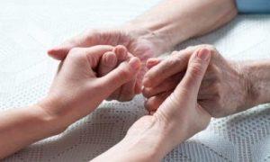 Volwassene zorgt voor ouder en houdt de handen vast