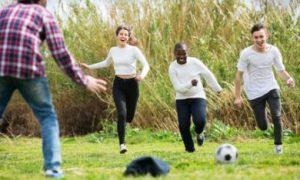 Een groep jongeren dat buiten voetbalt
