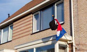 rugtas hangt aan de vlag buiten bij geslaagde examenkandidaat